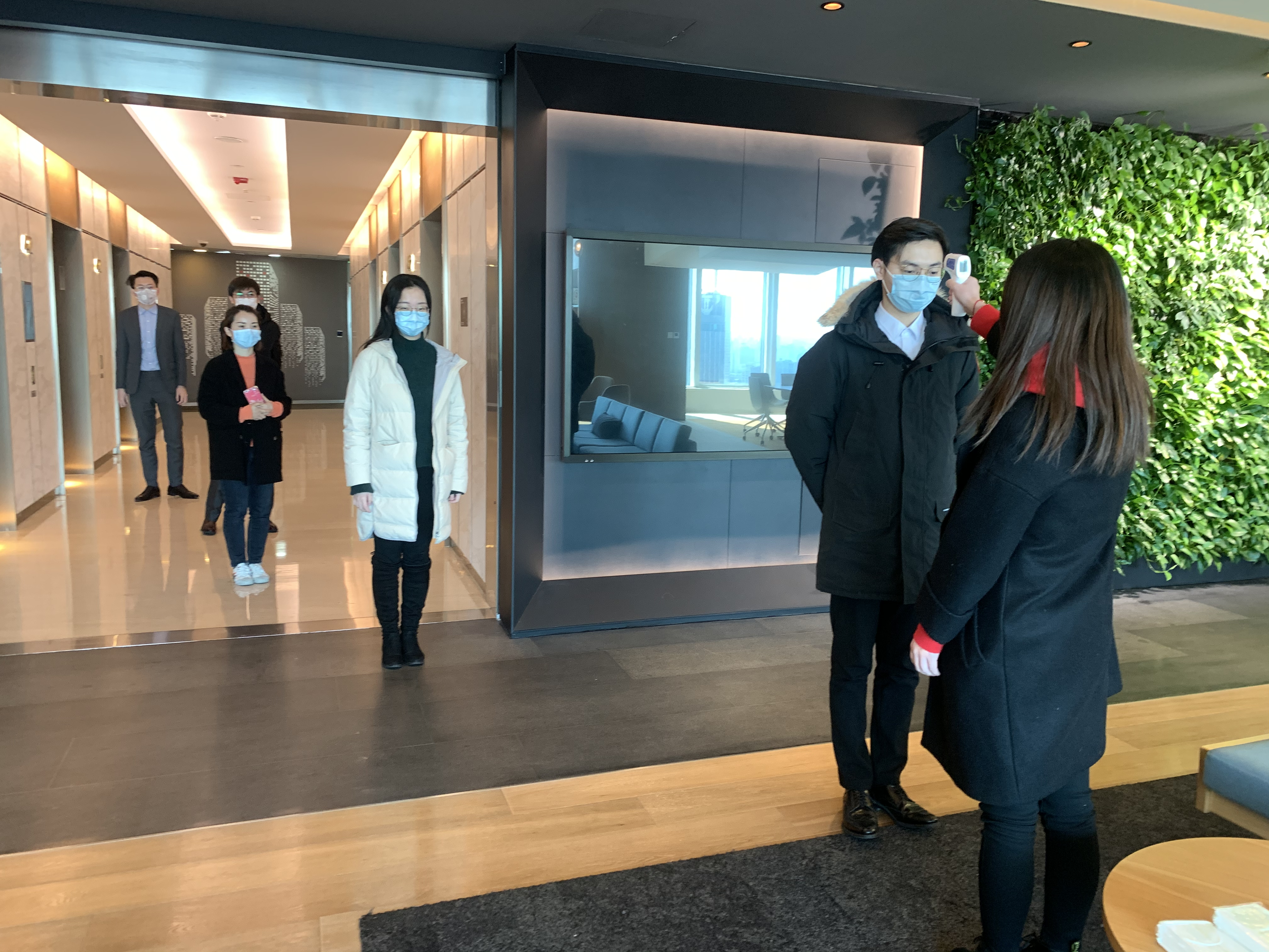 Employees at an office building in China have their temperatures checked. (Cushman & Wakefield)